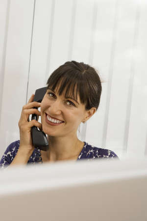 toils: Businesswoman sitting at desk in office, using telephone, smiling, portrait LANG_EVOIMAGES