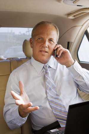 toils: Senior businessman sitting in back-seat of car, using mobile phone, gesturing with hand, portrait