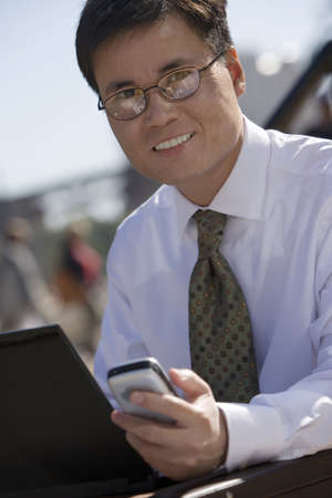 business: Businessman in spectacles using laptop and mobile phone, outdoors, smiling, portrait (tilt) LANG_EVOIMAGES