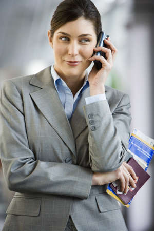 western european ethnicity: Businesswoman standing in airport terminal, holding ticket, using mobile phone, smiling, front view LANG_EVOIMAGES