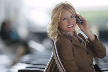 waistup: Businesswoman using mobile phone, smiling, side view, portrait LANG_EVOIMAGES