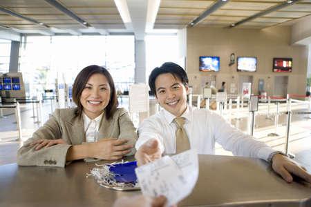 waistup: Pareja de negocios de registrarse en el aeropuerto, de negocios que reciben las tarjetas de embarque desde el check-in asistente, vista desde detr�s de mostrador de facturaci�n (enfoque diferencial)