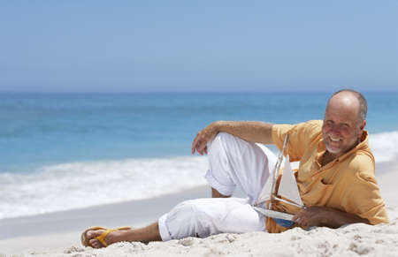 adult p senior man relaxing on sandy beach smiling side view portrait - Free Adult P