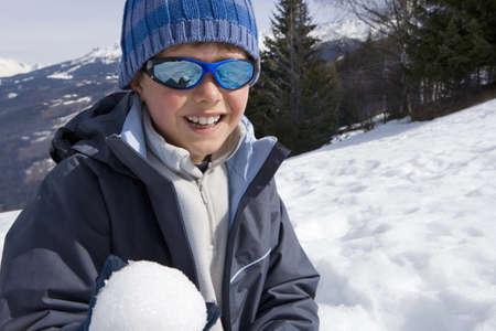 waistup: Boy (7-9) con el sombrero de lana y gafas de sol en el campo de nieve, que sostiene la bola de nieve, sonriente, retrato