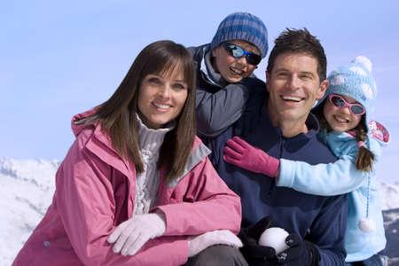 waistup: Familia de cuatro juntos en campo de nieve, sonriente, retrato, cordillera en el fondo
