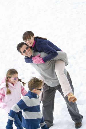 waistup: Pareja joven en el campo de nieve por el hijo y la hija (7-9), la mujer hombre que lleva en la espalda, sonriendo