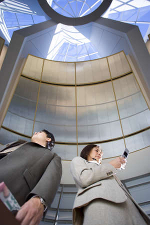 waistup: Businessman and woman standing below skylight in airport, woman using mobile phone, low angle view LANG_EVOIMAGES