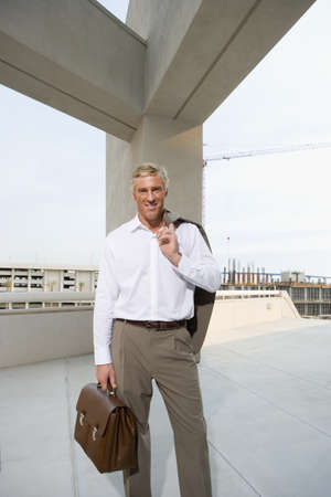 elevated view: Mature businessman, with briefcase, standing on elevated urban walkway below concrete beams, front view, portrait LANG_EVOIMAGES