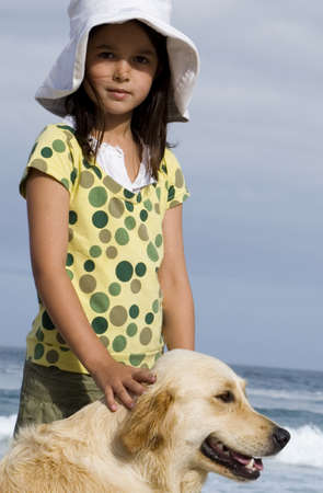 omnivores: Girl (6-8) in sun hat standing on beach with dog, smiling, side view, portrait
