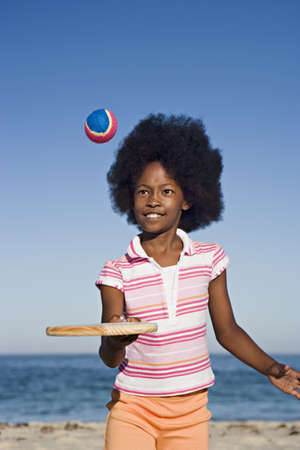 gratifying: Girl (8-10) playing with bat and ball on sandy beach, smiling, front view, portrait
