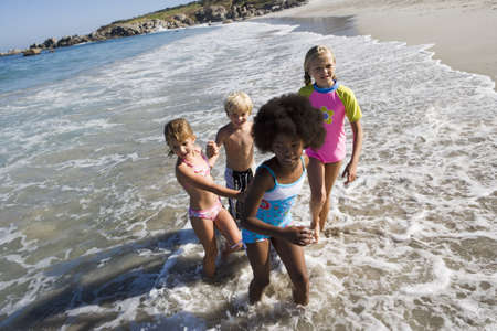 western slope: Four children (6-10) playing in Atlantic surf at beach, side view, smiling (wide angle, tilt)
