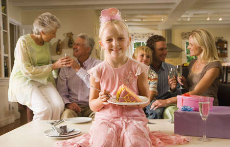 lavishly: Three generation family sitting on sofa at home, girl (4-6) sitting on coffee table with slice of birthday cake in foreground, smiling, front view, portrait