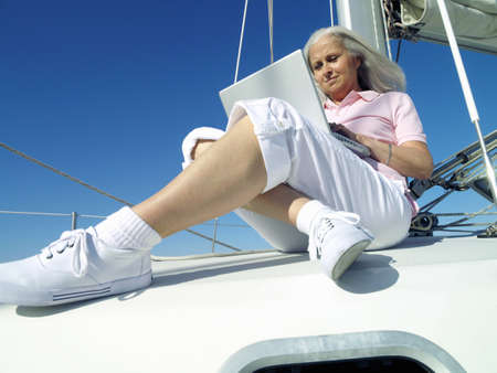 toils: Mature woman using laptop computer on boat, low angle view LANG_EVOIMAGES