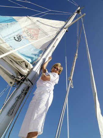 erecting: Mature woman erecting sail on boat, smiling, portrait, low angle view