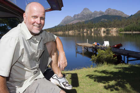 waistup: Mature man sitting in boot of parked SUV, smiling, side view, portrait, lake and jetty in background