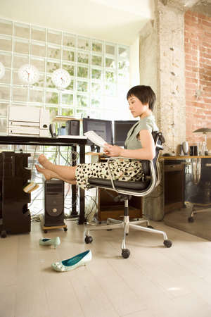 toils: Young woman reading paprerwork in office, barefeet resting on computer