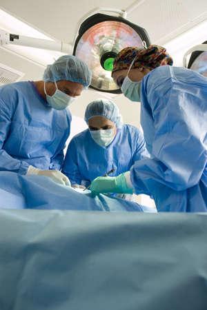 waistup: Cirujanos en batas y m�scaras quir�rgicas que operan en el paciente, vista de �ngulo bajo LANG_EVOIMAGES