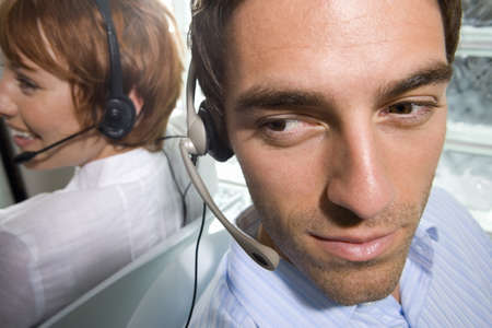 toiling: Businessman and woman wearing headsets sitting back to back, close-up, elevated view LANG_EVOIMAGES