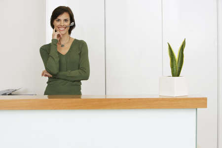 toils: Receptionist standing behind reception desk, wearing telephone headset, smiling, portrait