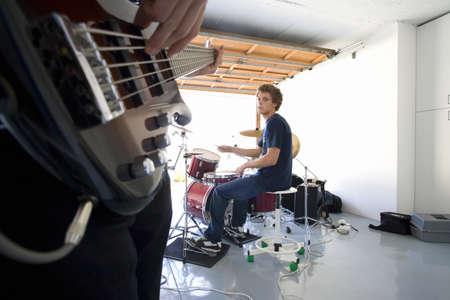 western european ethnicity: Teenage boy (16-18) playing drums in garage, looking at friend playing electric guitar in foreground