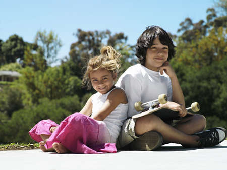 western european ethnicity: Boy (10-12) and girl (6-8) sitting in park, boy with skateboard in lap, smiling, portrait