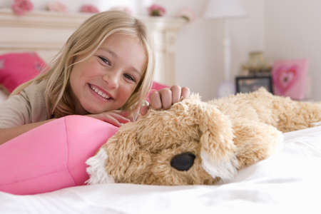 r furniture: Girl (6-8) on bed with toy dog, smiling, portrait