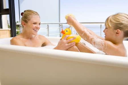 lavishly: Mother and daughter (6-8) in bath outdoors, woman with rubber duck, smiling at each other LANG_EVOIMAGES
