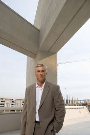 elevated view: Mature businessman standing on elevated urban walkway below concrete beams, front view, portrait LANG_EVOIMAGES