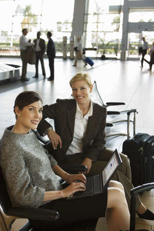 toiling: Two businesswomen waiting in airport departure lounge, woman using laptop, smiling, side view, portrait