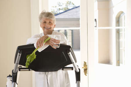 leant: Senior woman standing on treadmill, holding celery stick, smiling, portrait