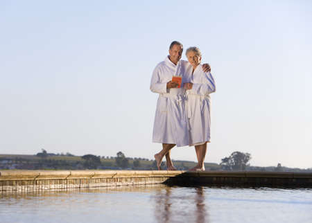 bath robes: Senior couple wearing white bath robes, embracing outdoors by swimming pool, smiling, portrait