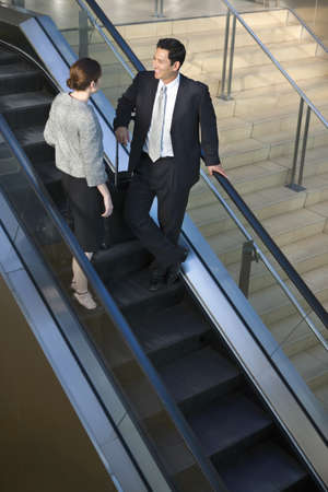 western european ethnicity: Businessman and woman standing on escalator in airport terminal, talking, elevated view LANG_EVOIMAGES