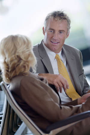 waistup: Businesswoman and businessman talking, smiling, side view (tilt)