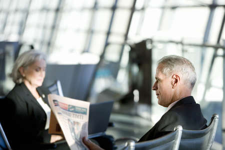 gentleman s: Businessman and woman sitting in airport departure lounge, woman using laptop, man reading financial newspaper, side view