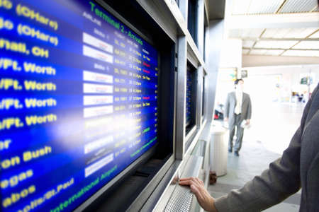 leant: Businessman standing beside flight information screen in airport, close-up, side view, mid-section LANG_EVOIMAGES
