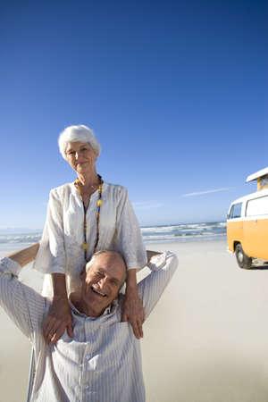 waistup: Pares mayores en la playa por campista furgoneta, sonriente, retrato