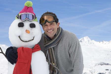 waistup: Joven de pie por el mu�eco de nieve, sonriente, retrato