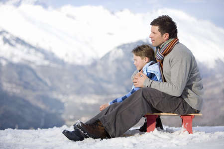 gentleman's: Father and son (7-9) sitting on sled in snow field, side view, mountain range in background