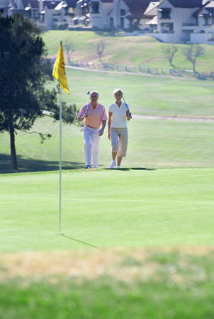 western slope: Mature couple playing golf, approaching putting green in mid-distance, front view, focus on background