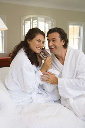 western european ethnicity: Couple wearing white bath robes on bed, both holding telephone receiver, smiling