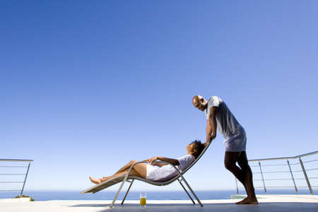 lavishly: Young man standing by young woman lying on deck chair by sea, smiling at each other, side view LANG_EVOIMAGES