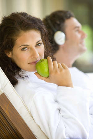 western european ethnicity: Couple relaxing on deck chairs, portrait of woman holding green apple, smiling