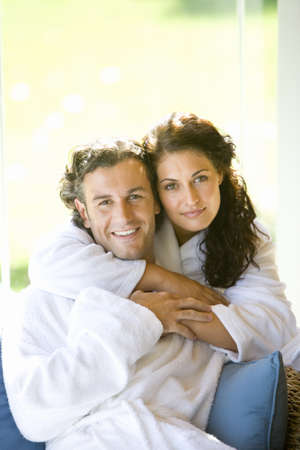 western european ethnicity: Couple wearing white robes, embracing, smiling, portrait