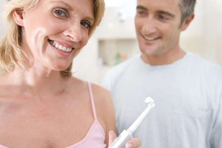 confide: Couple standing in bathroom, woman holding up toothbrush, smiling, portrait LANG_EVOIMAGES