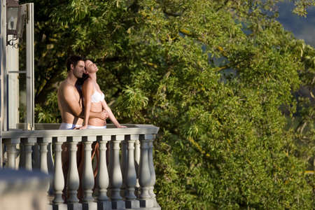 western european ethnicity: Young couple wearing underwear, embracing on balcony, side view