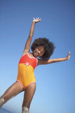 gratifying: Girl (8-10) in orange swimsuit standing on beach, raising arms in air, smiling, portrait (tilt)