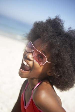 gratifying: Girl (8-10) standing on beach in sunglasses, shouting, side view, portrait (tilt) LANG_EVOIMAGES