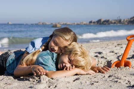waistup: Boy (4-6) y una ni�a (7-9) en la playa de arena al lado de naranja pala, sonriendo, vista lateral LANG_EVOIMAGES