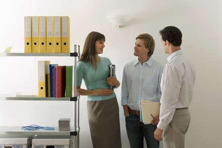 western european ethnicity: Three business colleagues standing beside shelf in office, talking