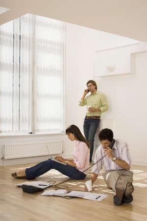 western european ethnicity: New business partners working in empty office, woman using laptop on floor, two men using phones